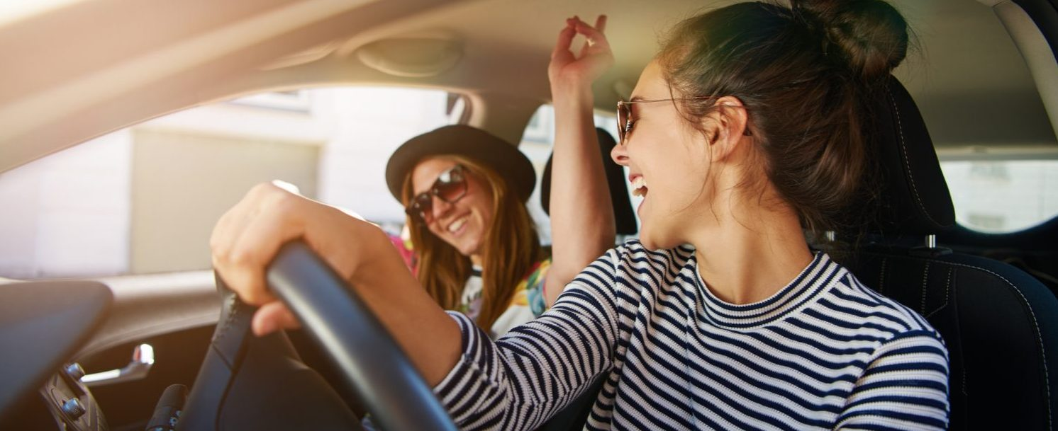 Two young women having fun driving along the street laughing and joking with the driver distracted looking at her passenger - Weekend Getaways in PA for Girlfriends