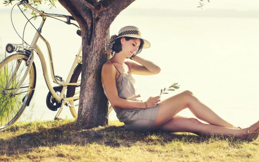 Beautiful dormant woman in love waiting under a tree by the lake with a bike by her side